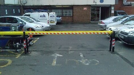 Automatic sliding barrier in closed position across the entrance to a car park