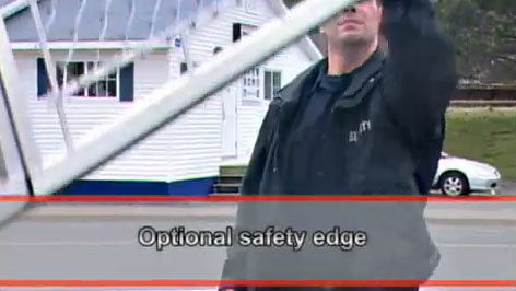 Man demonstrating safety edge on a rising fence traffic barrier