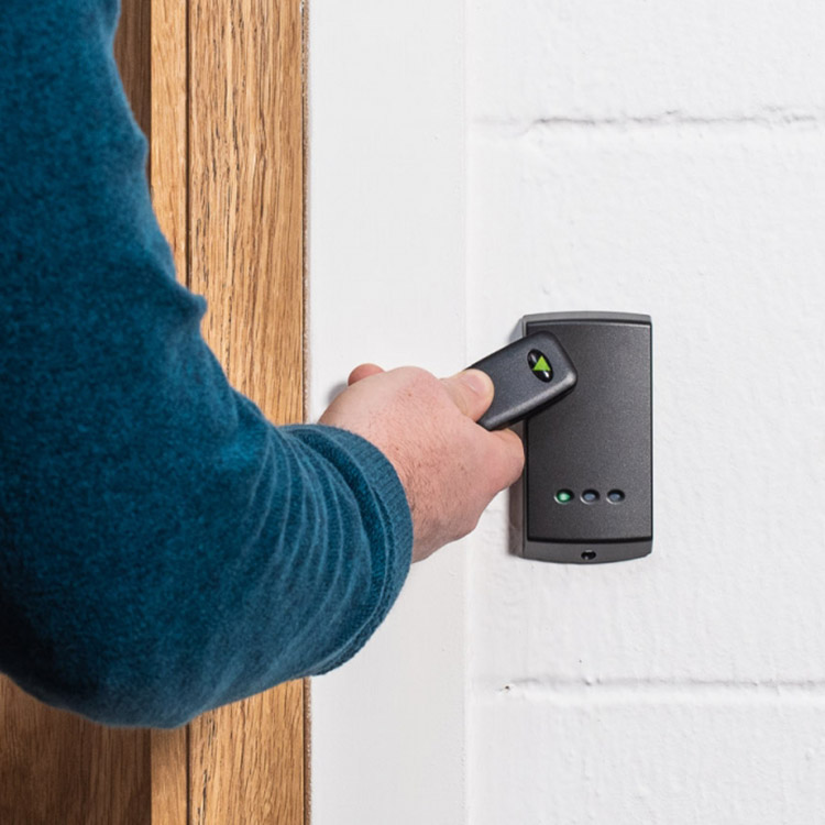 Photo of person using an RFID fob to gain access to a room