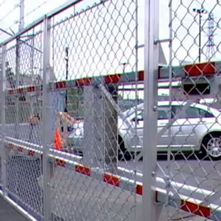 Automatic rising fence barrier controlling access to a private car park