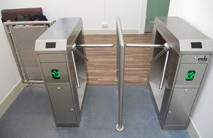 Row of half height turnstiles with directional arrows