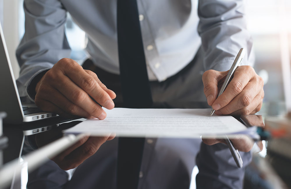 Photo of a person signing an agreement