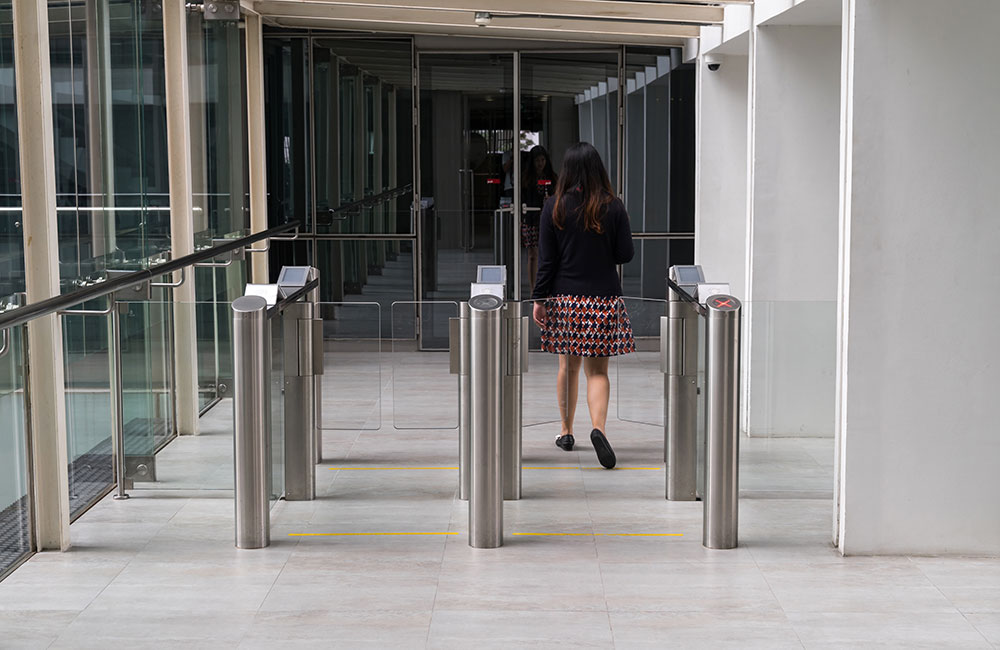 Photo of glass walls and glass turnstile gates in an office building