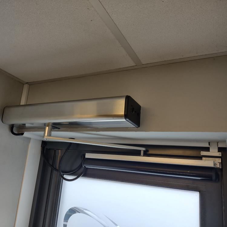 Photo of automatic door opener mounted on an external office door.