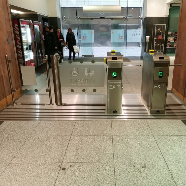 Photo of pair of stainless steel half height turnstiles with wide disabled access gate