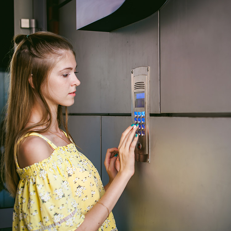 Woman using a wall mounted keypad entry system