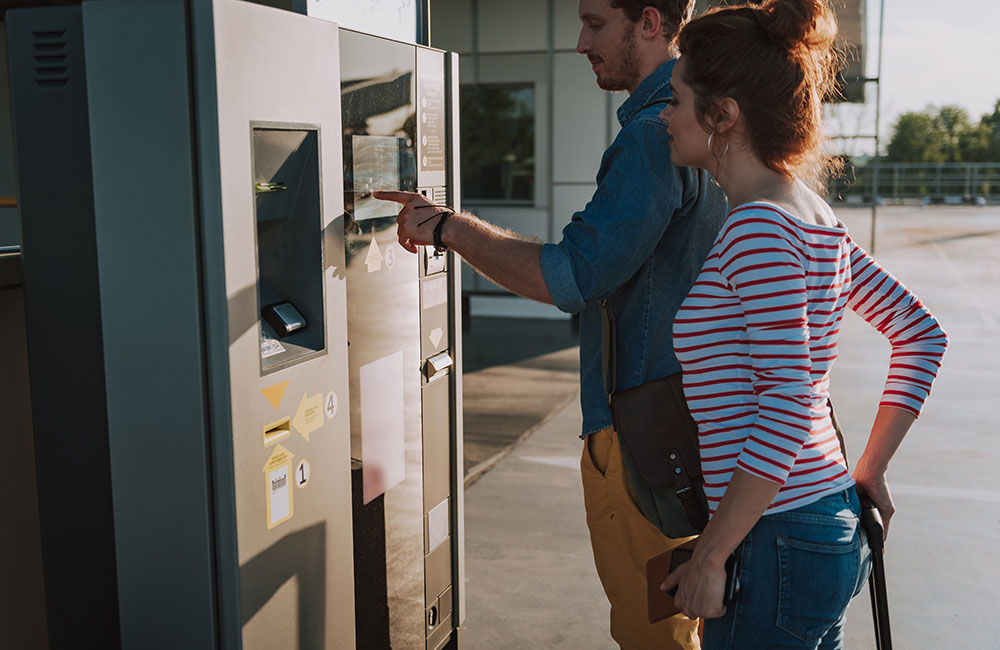 Photo of people using a pay on foot parking ticket machine