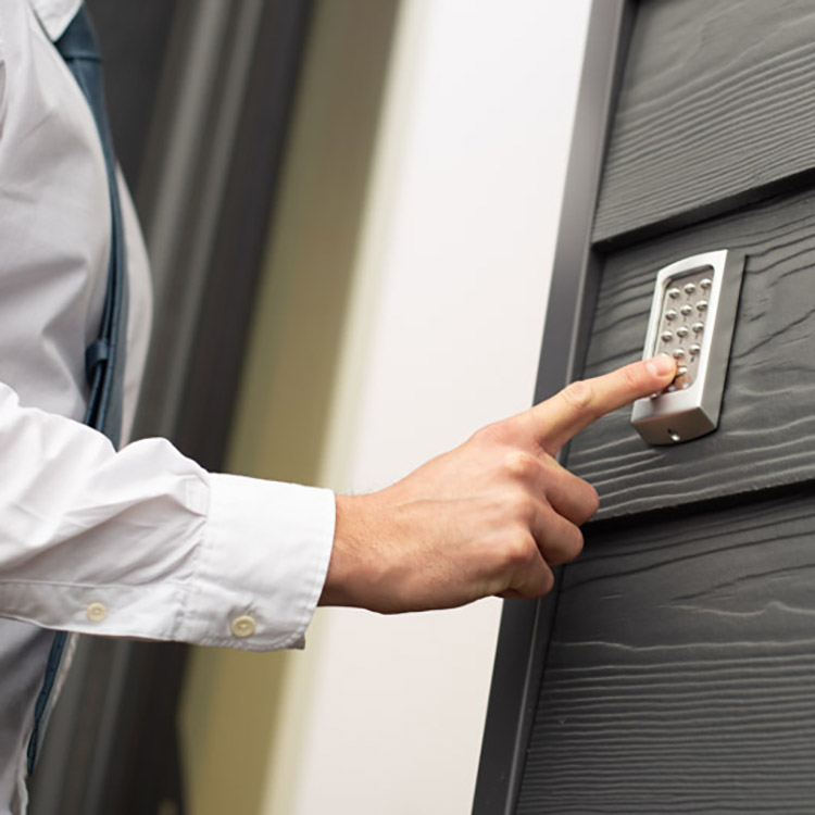 Photo of person using keypad to gain access through a door