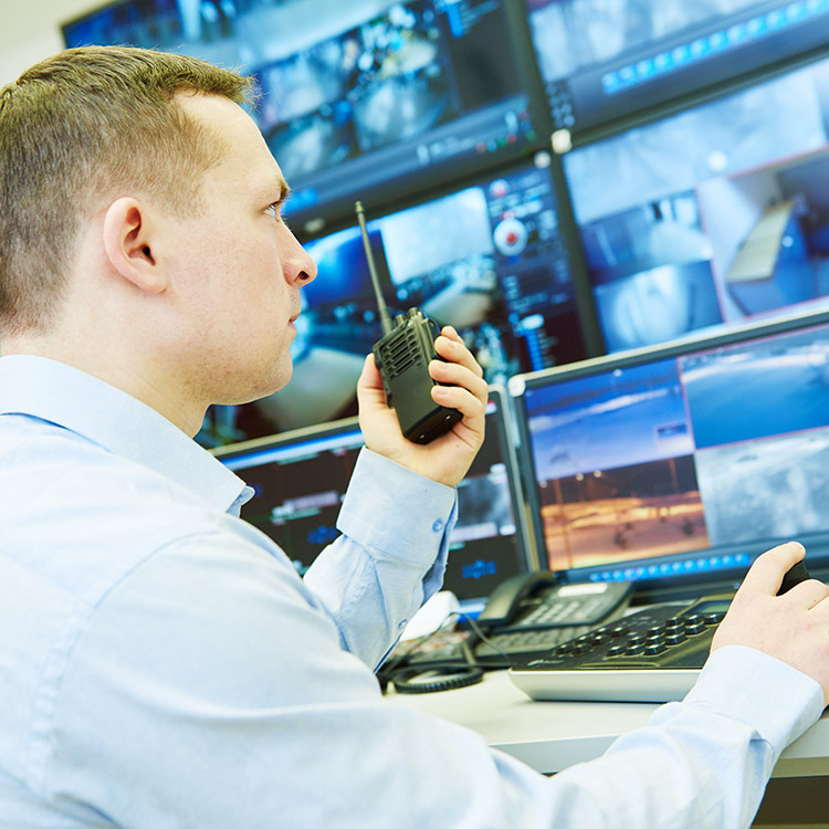 Security guard in monitoring centre using handheld radio and controlling CCTV cameras