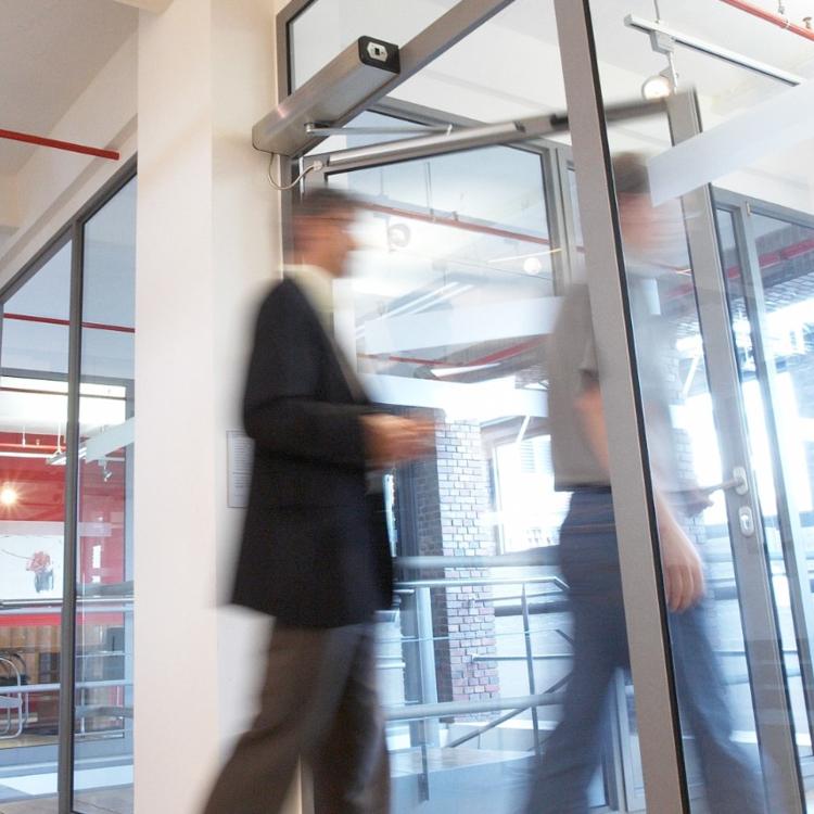 Photo of people walking through a door with an automatic door opener