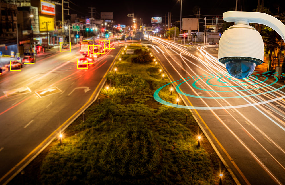 Photo of a CCTV camera overlooking a busy road at night
