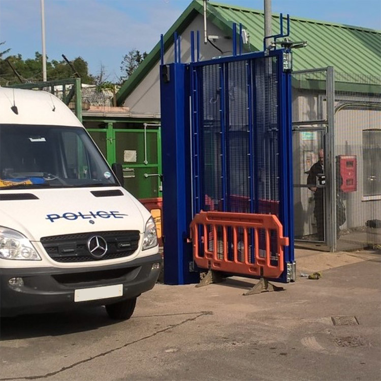 Photo of police van leaving a site through secure bifolding gates