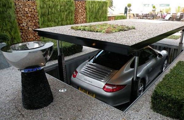 Photo of a Porsche on a car lift integrated into driveway