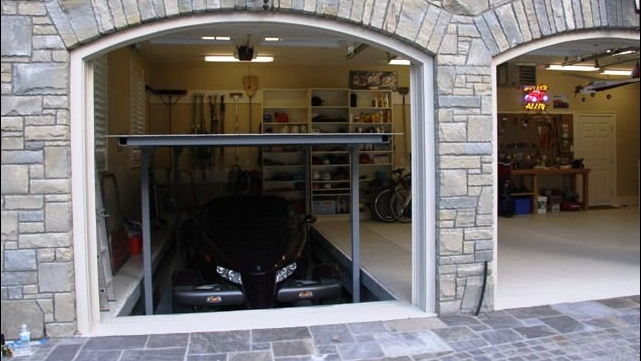 Automatic rising car lift in garage