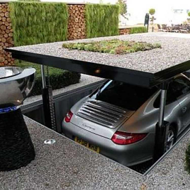 Car lift with Porsche descending underneath driveway