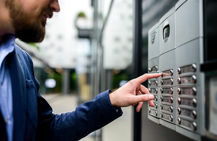 Man using wireless intercom to contact an apartment