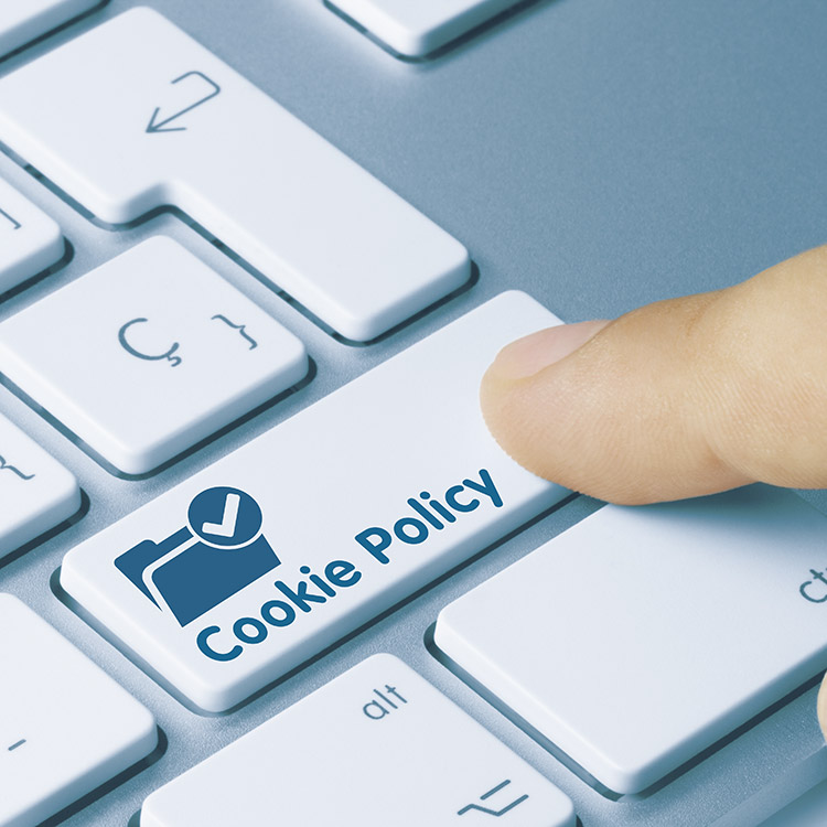 """Person pressing button on keyboard labelled """"Cookie Policy"""""""