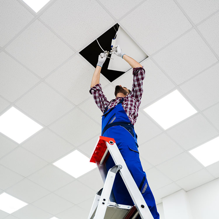 Electrician working on cables above ceiling tiles