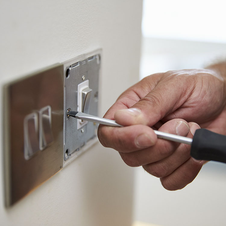 Electrician installing a plug socket in a wall