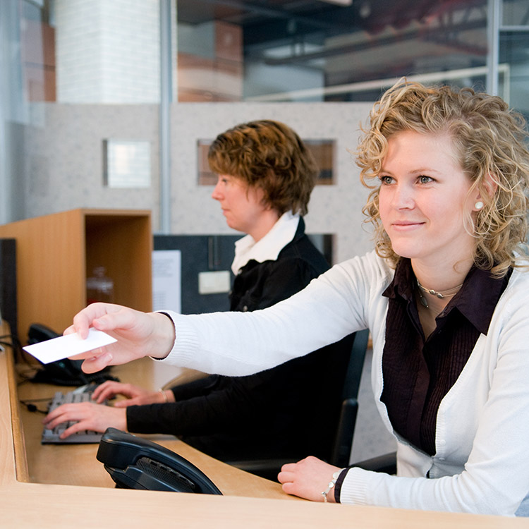 Photo of receptionist passing an access control key card to a guest