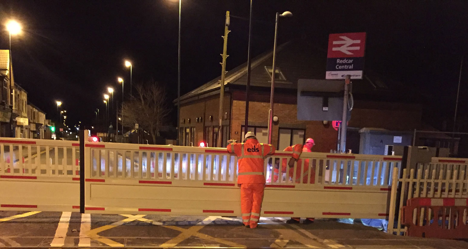 Photo of EDS operatives inspecting level crossing gates during installation.