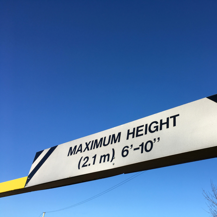 """""""Maximum height 2.1m"""" sign on a barrier"""