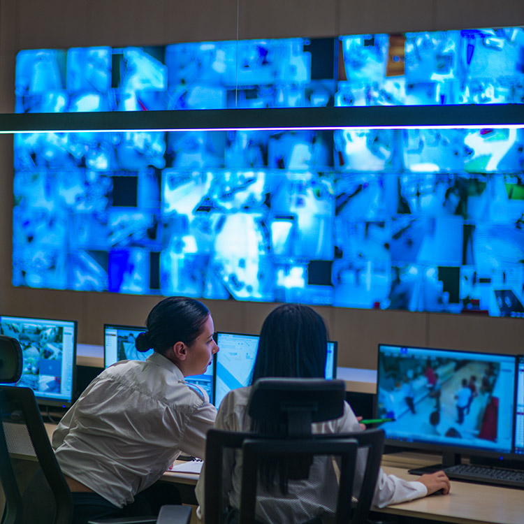 Two security guards watching CCTV footage in a control room