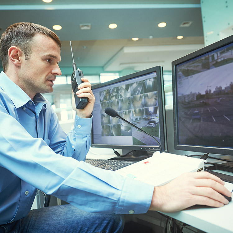 Photo of man with handheld radio monitoring CCTV feeds in a security operating centre