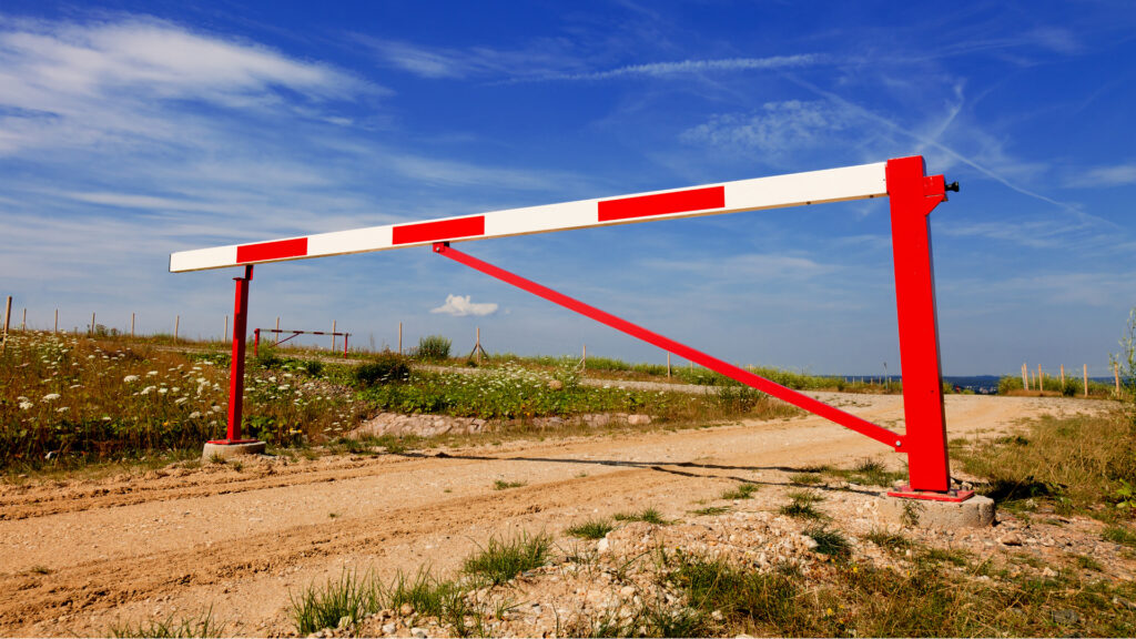Swinging barrier blocking access to rural track